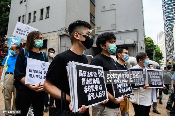 """Pro-democracy protesters hold placards that translate as """"National Security Law comes to Hong Kong, Hong Kong becomes Xinjiang, Stanley Prison..."""