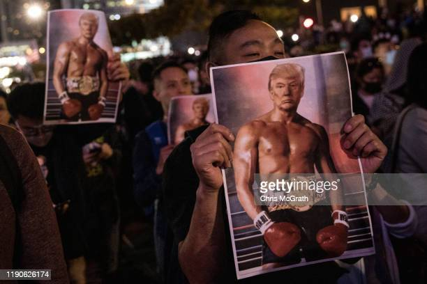 Prodemocracy protesters hold posters of US President Donald Trump during a Thanksgiving Day rally at Edinburgh Place on November 28 2019 in Hong Kong...