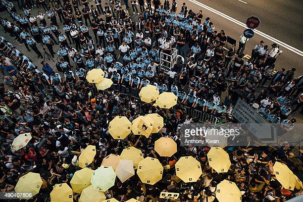 Prodemocracy protesters hold umbrellas in front of police cordon line outside of the Hong Kong Government Complex at Admiratly district on September...