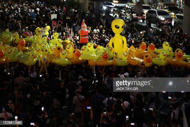 Pro-democracy protesters hold up large inflatable yellow ducks, which have recently become a symbol of the demonstrations, and other inflatable...