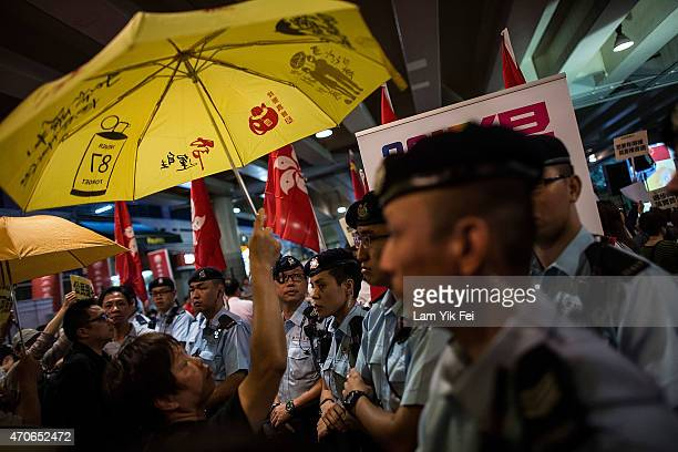 Prodemocracy protesters hold yellow umbrellas a symbol of the prodemocracy protests protest during Hong Kong Chief Executive Leung Chunying visit to...