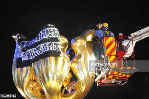 Pro-democracy protesters is removed by police officers from the golden bauhinia statue ahead of the 20th anniversary of Hong Kong's handover to China...