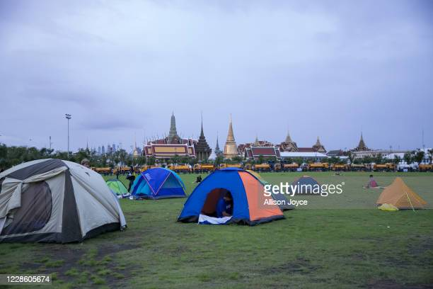 Pro-democracy protesters look out of their tents early in the morning by Sanam Luang field during an overnight rally on September 20, 2020 in...