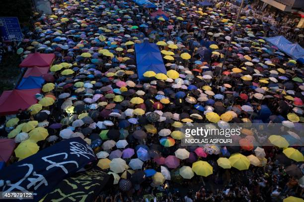 Pro-democracy protesters open their umbrellas to mark one month since they took the street, in the Admiralty district of Hong Kong on October 28,...