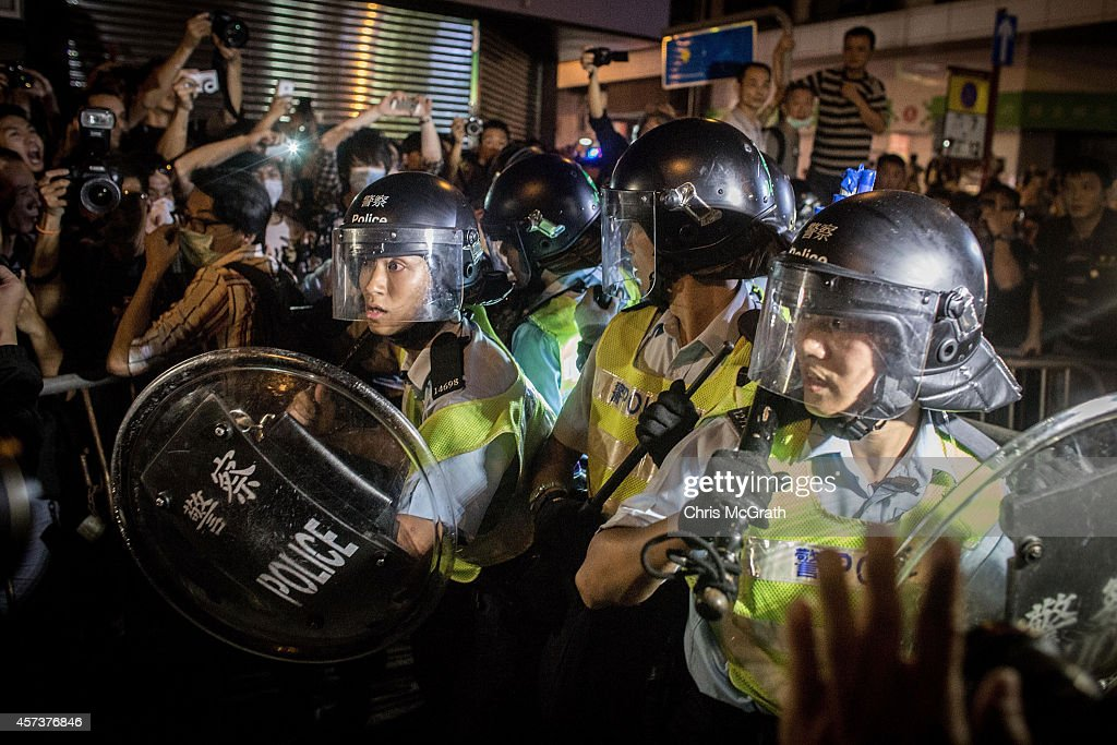 Pro-democracy protesters push police back as they break down barricades and take back streets in Mong Kok on October 18, 2014 in Hong Kong, Hong Kong. Police have begun to take measures to remove the blockades put in place by pro democracy supporters following weeks of protests. Hong Kong's Chief Executive Leung Chun-ying today called for talks to resume between protest groups and government officials and said his government is ready to meet with student leaders to discuss 'universal suffrage'
