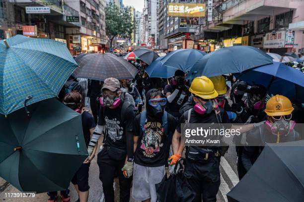 Prodemocracy protesters react as police fire tear gas during a clash at a demonstration in Admiralty district on October 6 2019 in Hong Kong China...