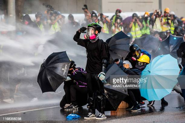 Pro-democracy protesters react as police fire water cannons outside the government headquarters in Hong Kong on September 15, 2019. - Hong Kong riot...