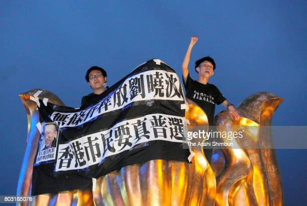 Prodemocracy protesters shout slogan on the golden bauhinia statue ahead of the 20th anniversary of Hong Kong's handover to China on June 28 2017 in...