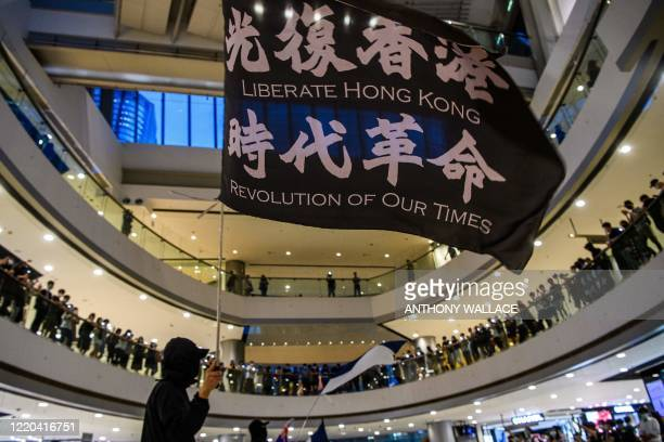 Prodemocracy protesters shout slogans and wave flags as they gather in a shopping mall in Hong Kong on June 16 2020