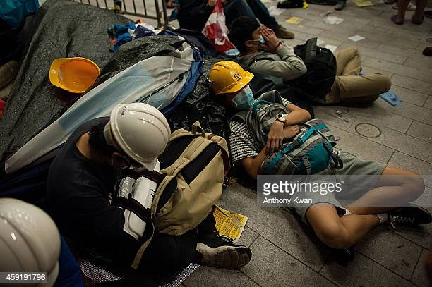 Prodemocracy protesters sleep on the floor outside the Legislative Council building after clashes with prodemocracy activists on November 19 2014 in...