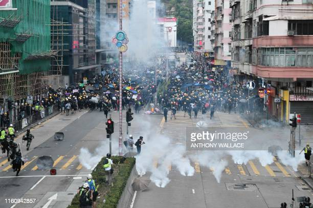 TOPSHOT ProDemocracy protesters throw back tear gas fired by the police during a demonstratrion against the controversial extradition bill in Sham...