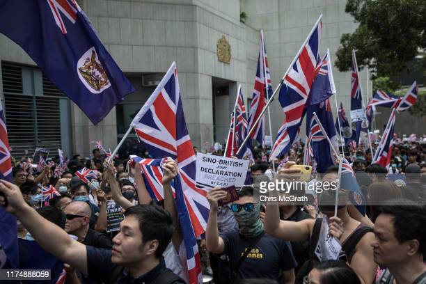 Prodemocracy protesters wave flags and chant slogans outside the UK embassy on September 15 2019 in Hong Kong China Prodemocracy protesters have...