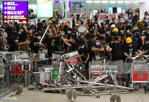TOPSHOT Prodemocracy protestors block the entrance to the airport terminals after a scuffle with police at Hong Kong's international airport late on...