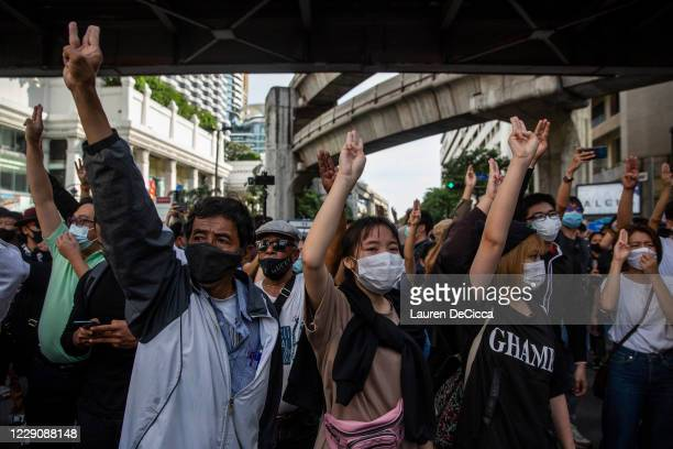 Pro-democracy protestors hold up a three finger salute at the Ratchaprasong intersection on October 15, 2020 in Bangkok, Thailand. Thousands of...