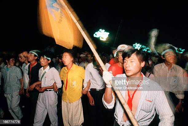 Prodemocracy student demonstrators march their way towards Tiananmen Square as they lead the procession that is carrying the 'Goddess of Democracy'...