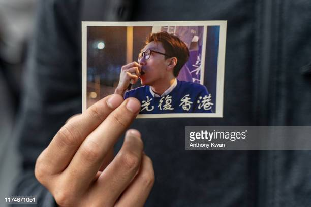 October 9: A pro-democracy supporter holds a portrait of activist Edward Leung as supporters gather outside the High Court premises in support of...