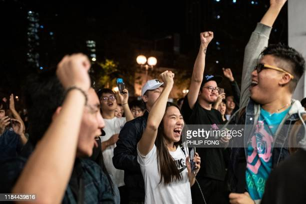 Prodemocracy supporters chant as they celebrate after proBeijing candidate Junius Ho lost a seat in the district council elections in Tuen Mun...