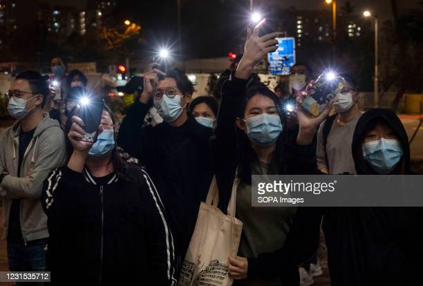 Pro-democracy supporters hold up their cellphone light after 4 democracy activists were released on bail at the West Kowloon court buildings in Hong...