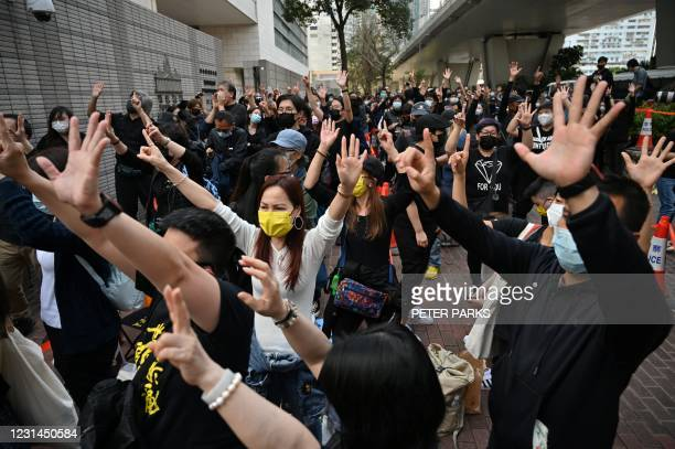 Pro-democracy supporters make hand signs outside the West Kowloon court in Hong Kong on March 1 ahead of court appearances by dozens of dissidents...