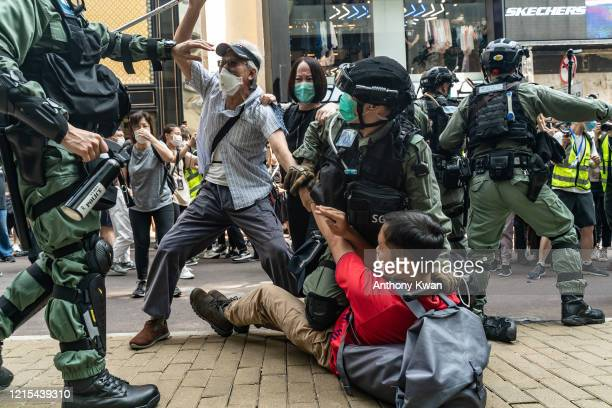 Prodemocracy supporters scuffle with riot police during an detention at a rally in Causeway Bay district on May 27 2020 in Hong Kong China Chinese...