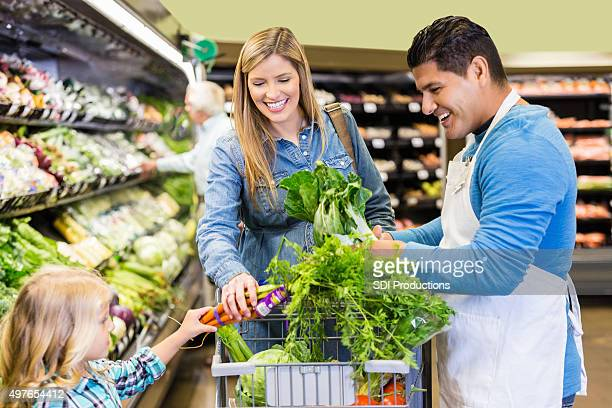 Produce manager asisstingn customer and her daughter in supermarket