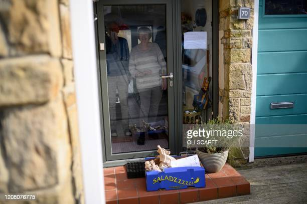 Produce order from the community owned grocery shop, The Village Green, is left on the doorstep of local residents self-isolating amidst the novel...