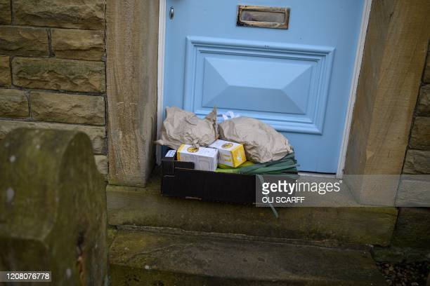 Produce order from the community owned grocery shop, The Village Green, is left on the doorstep of a local resident self-isolating amidst the novel...