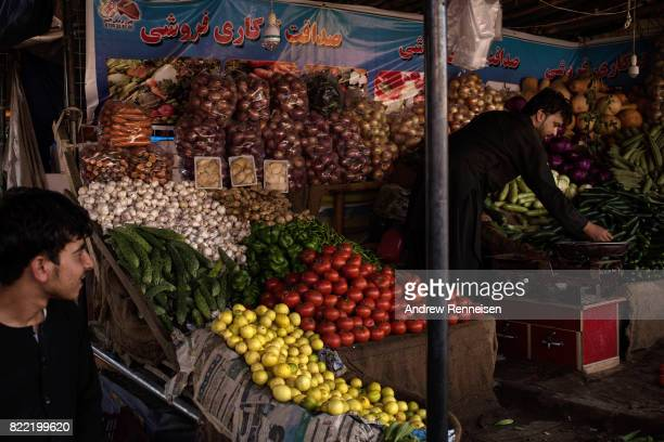 A produce vendor weighs cucumbers in a bazaar in Kabul's old city neighborhood on July 20 2017 in Kabul Afghanistan Despite a heavy security presence...