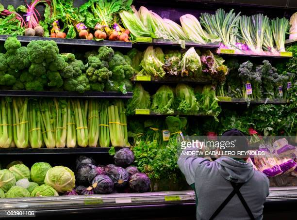 A produce worker stocks shelves near romaine lettuce at a supermarket in Washington DC on November 20 2018 US health officials warned consumers not...