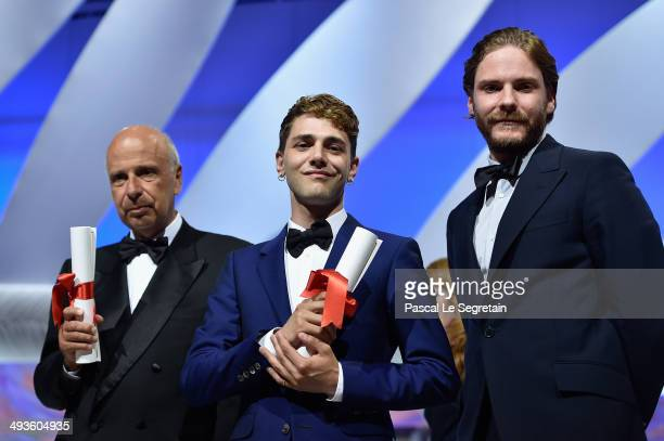 Producer Alain Sarde and director Xavier Dolan pose on stage with actor Daniel Bruhl after jointly winning the Jury Prize for 'Mommy' and 'Adieu au...