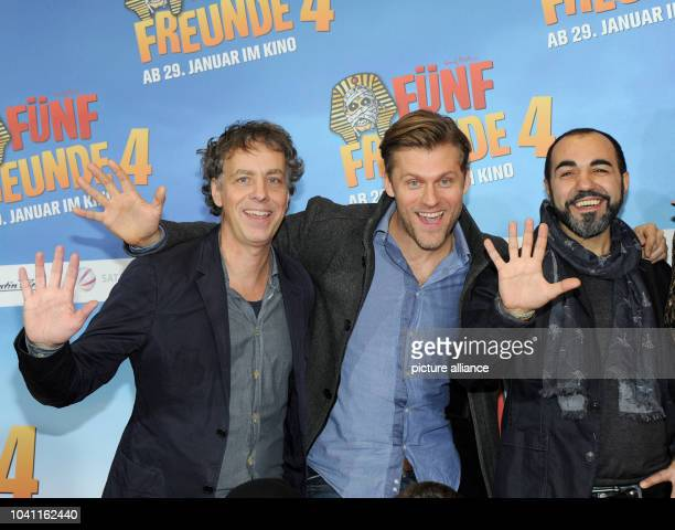 Producer Andreas UlmkeSmeaton and actors Jens Atzhorn and Adnan Maral pose in front of the movie poster at the premiere of 'Fuenf Frende 4' at the...