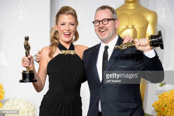 Producer Caitrin Rogers and director Morgan Neville pose in the press room during the Oscars at Loews Hollywood Hotel on March 2 2014 in Hollywood...