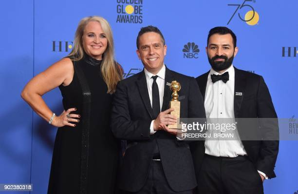Producer Darla K Anderson director Lee Unkrich and Adrian Molina pose with the Best Motion Picture Animated trophy for Coco during the 75th Golden...