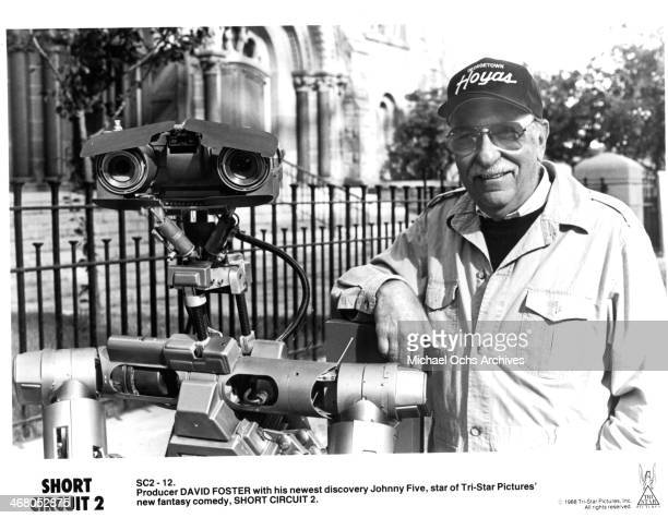 """Producer David Foster poses with Johnny Five on set of the movie """"Short Circuit 2"""", circa 1988."""