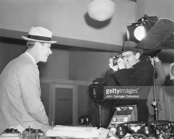 Producer David L Loew takes a picture of actor Joe E Brown between scenes of Riding on Air
