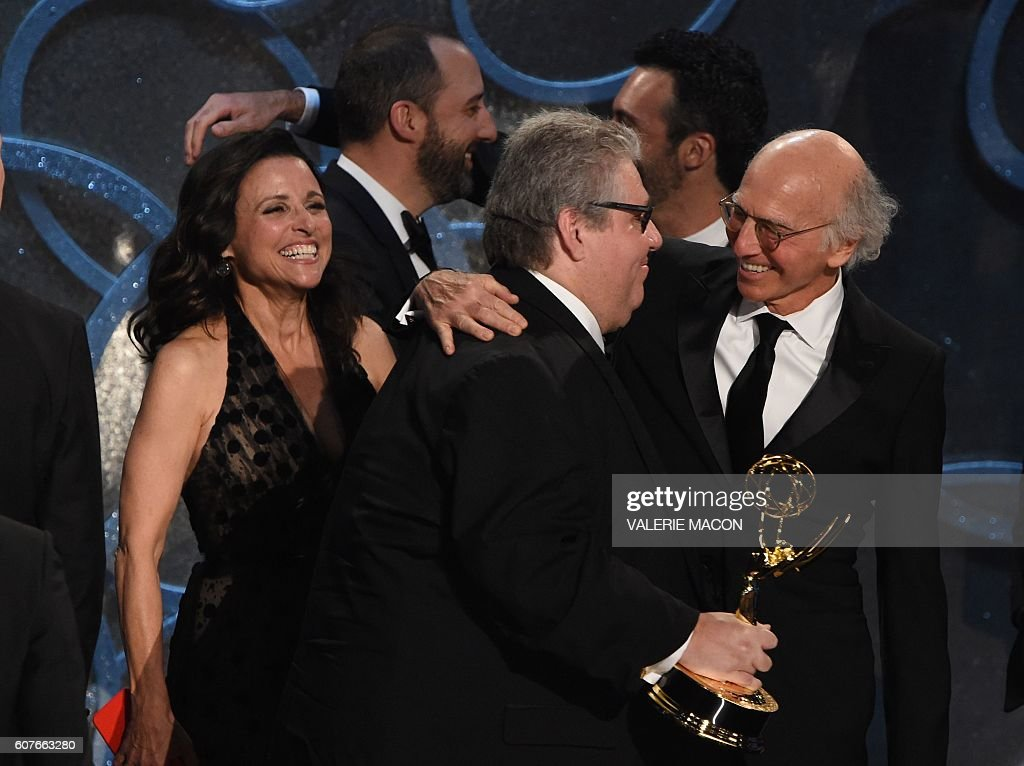 Producer David Mandel (2L) accepts Outstanding Comedy Series for 'Veep' from actor Larry David during the 68th Emmy Awards show on September 18, 2016 at the Microsoft Theatre in downtown Los Angeles. / AFP / Valerie MACON