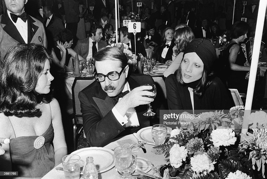 Producer David Merrick (1911 - 2000) sits at a table between two unidentified women during a formal event, 1970s.