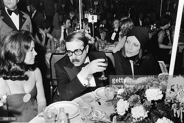 Producer David Merrick sits at a table between two unidentified women during a formal event 1970s