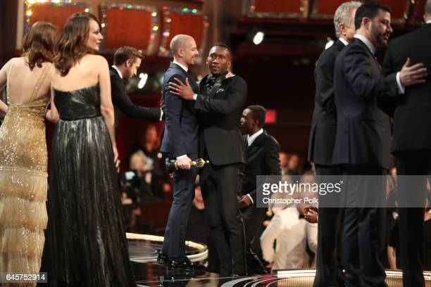 Producer Fred Berger and actor Mahershala Ali embrace onstage following the error with the Best Picture award during the 89th Annual Academy Awards...