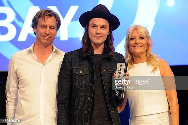 Producer Giles Martin Singer James Bay with his Best Newcomer award and host Gaby Roslin on stage at the Nordoff Robbins O2 Silver Clef awards at The...