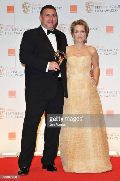Producer Graham King and actress Gillian Anderson pose in the press room with the Animated Film award for 'Rango' during the Orange British Academy...