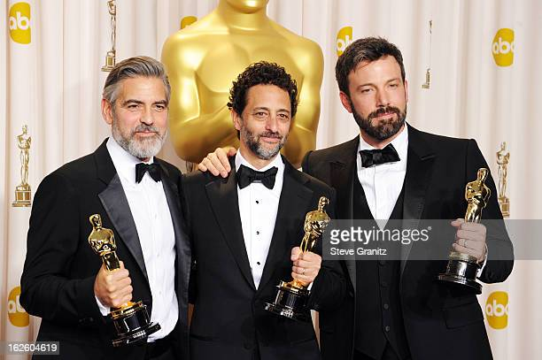 Producer Grant Heslov, actor/producer Ben Affleck and actor/producer George Clooney pose in the press room during the Oscars at the Loews Hollywood...