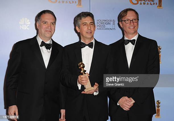 Producer Jim Taylor directorproducer Alexander Payne and producer Jim Burke pose in the press room at the 69th Annual Golden Globe Awards held at the...