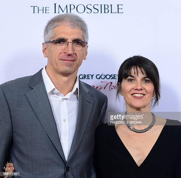 Producer Maria Belon and her husband Enrique pose on arrival for the Los Angeles premiere of the film 'The Impossible' on December 10 2012 in...