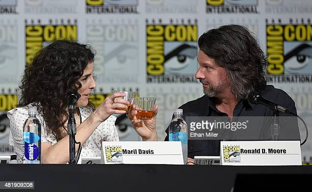 """Producer Maril Davis and writer/producer Ronald D. Moore share a toast at the Starz: """"Outlander"""" panel during Comic-Con International 2015 at the San..."""