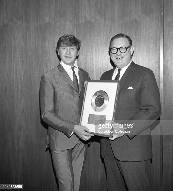 Producer Mickie Most receives a gold record award from Mort Nasatir at MGM Records on April 17 1967 in New York