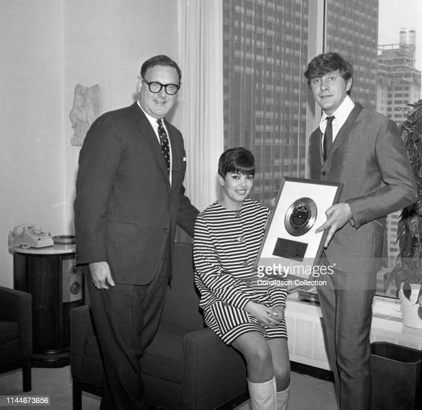 Producer Mickie Most receives a gold record award with his wife Christina Hayes from Mort Nasatir at MGM Records on April 17 1967 in New York