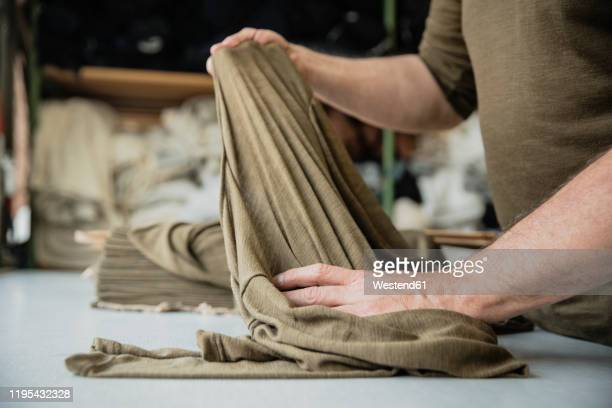 producer of a fashion label during control of fabric in a circular knitting mill - 織物工場 ストックフォトと画像