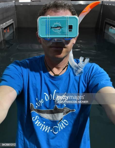 Producer of The Dolphin Swim Club Benno Brada wearing a Virtual Reality headset leaves a pool during the 'Laval Virtual' virtual reality augmented...