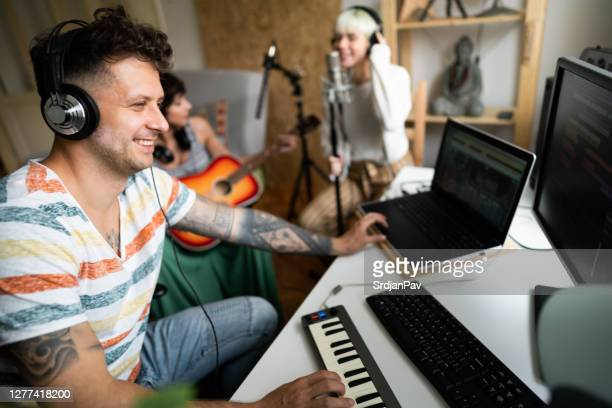 音楽スタジオでキーボードを演奏し、ボーカルとギターを録音するプロデューサー - キーボード奏者 ストックフォトと画像